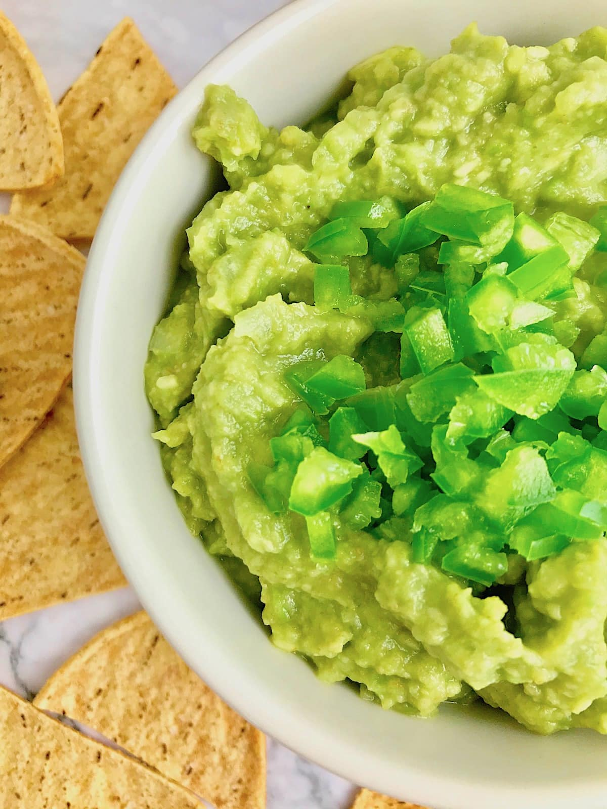 Tortilla chips on a table next to half of a bowl of guacamole topped with chopped green jalapeno pepper.