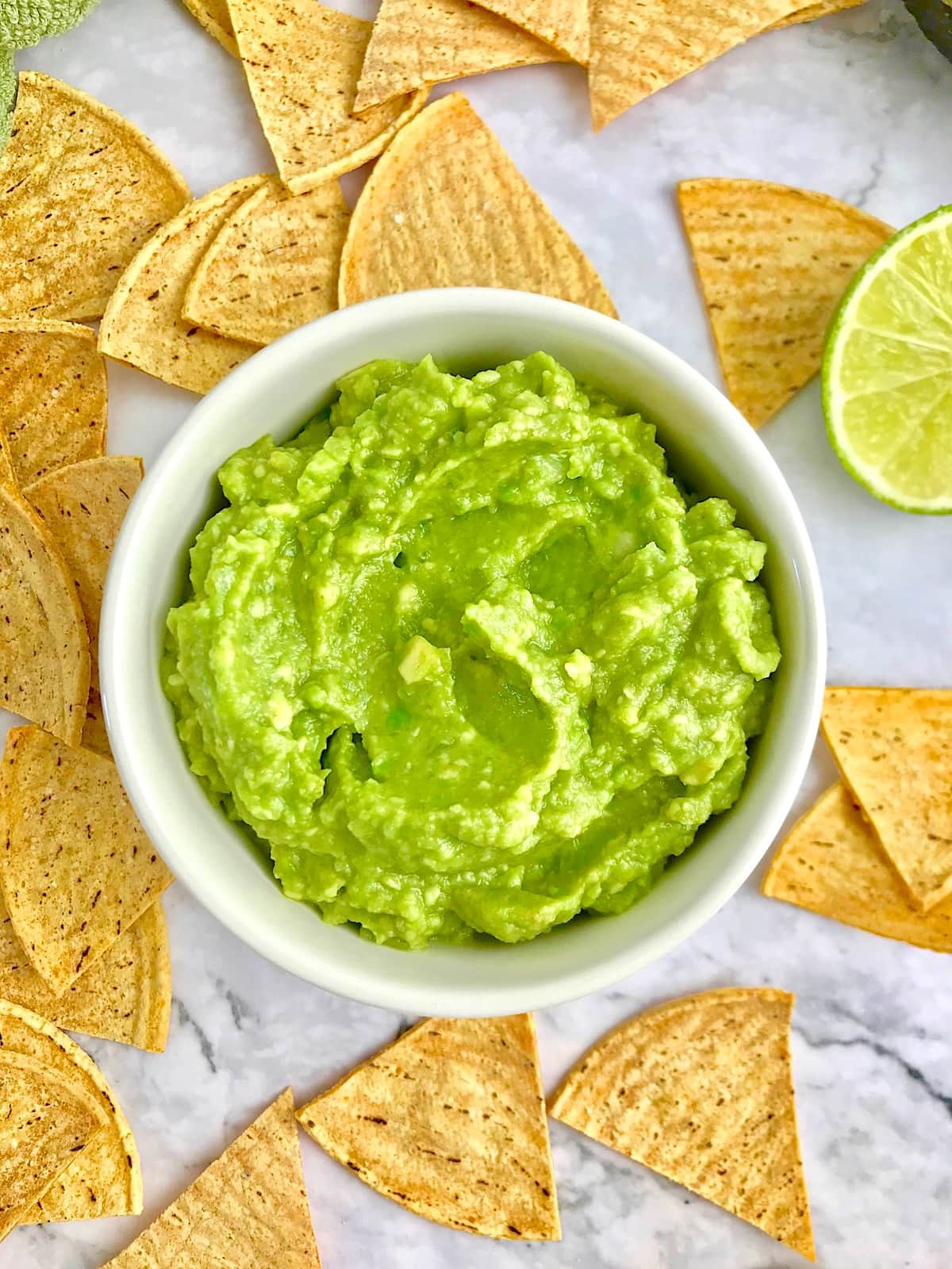 Green guacamole in a white dish, surrounded by tortilla chips.