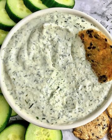 Tzatziki with a cracker dipped into it surrounded by more crackers and cucumber slices on a table.