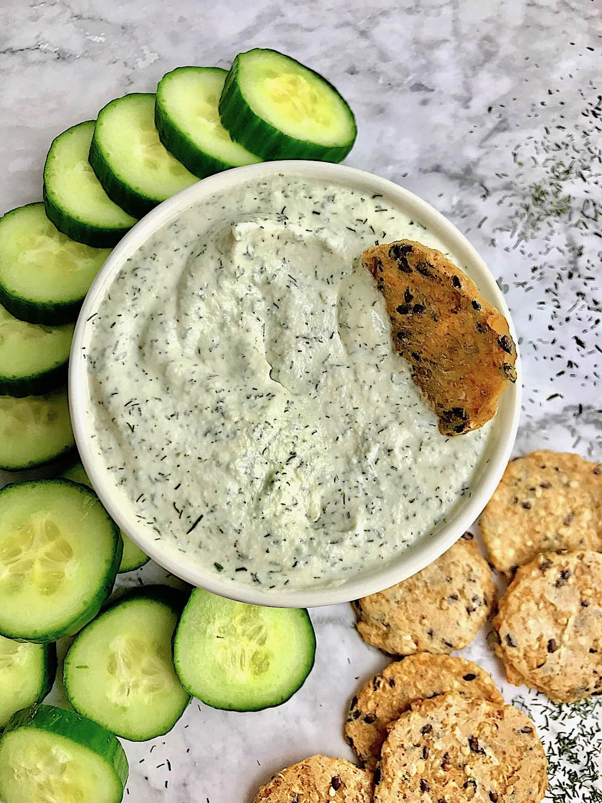 Tzatziki surrounded by cucumber slices and crackers on a table with dill sprinkled on it.