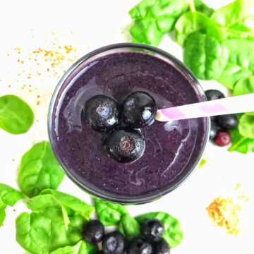 Overhead of a smoothie with blueberries on top and spinach leaves on the table in the background.
