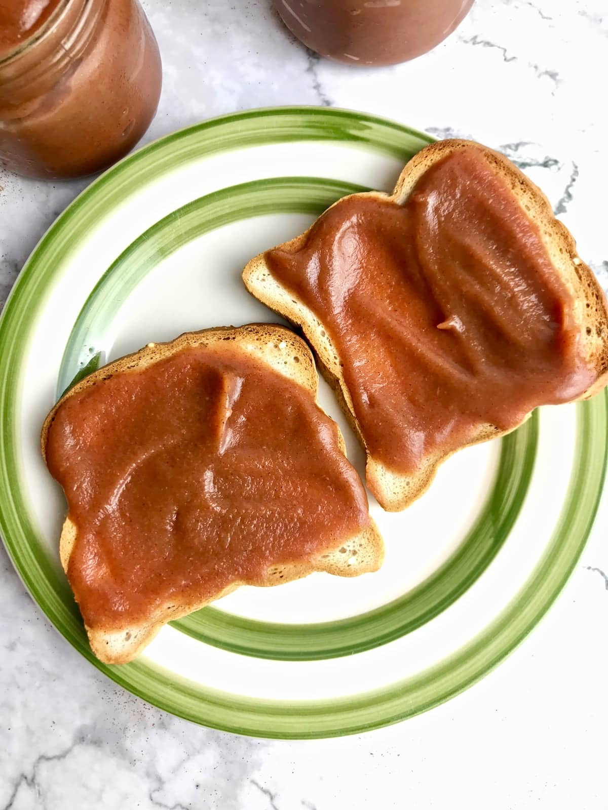 Two pieces of toast topped with apple butter on a white plate with a green rim.