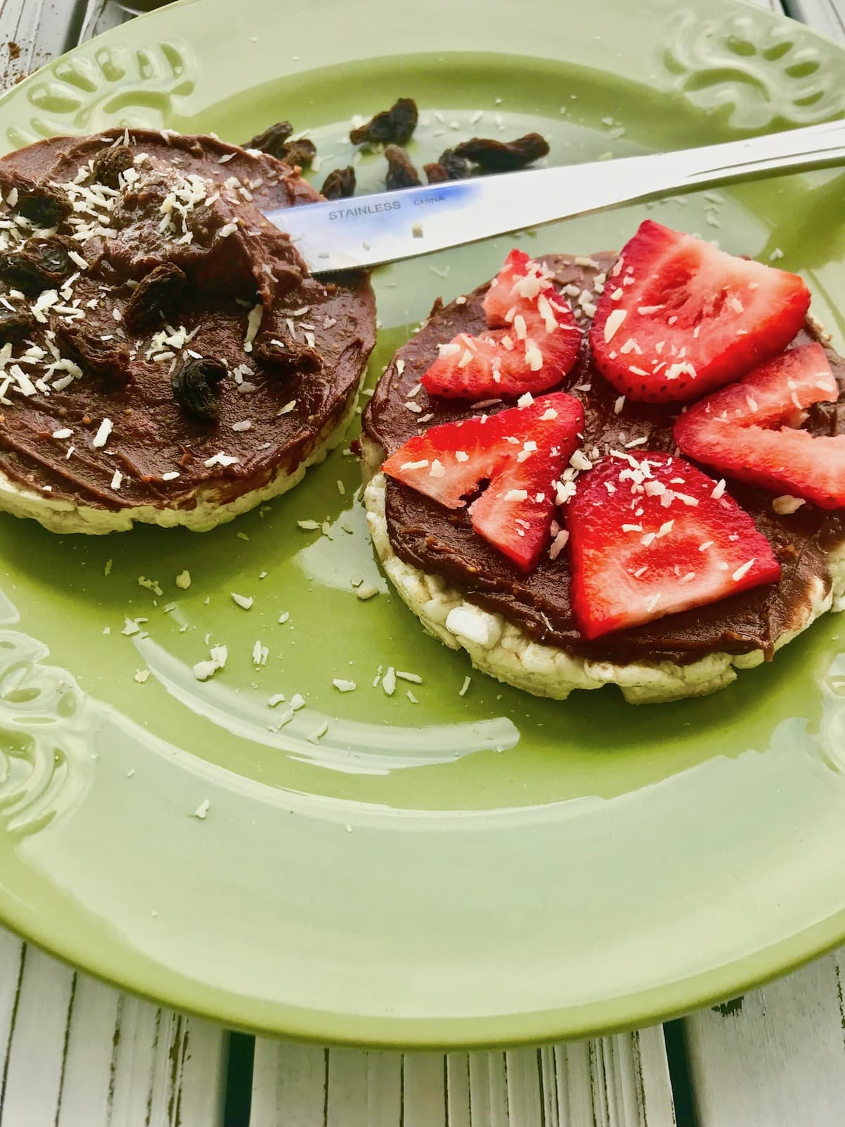Chocolate peanut butter spread on rice cakes, topped with strawberries, raisins, and coconut flakes.