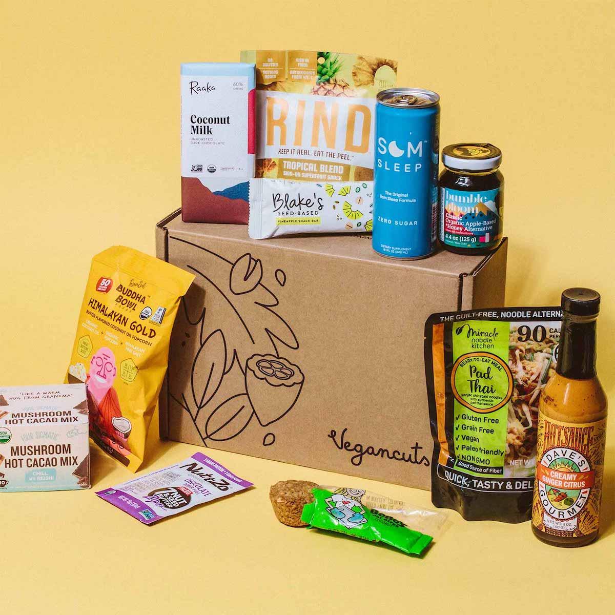 Several vegan snack items surrounding a cardboard box.