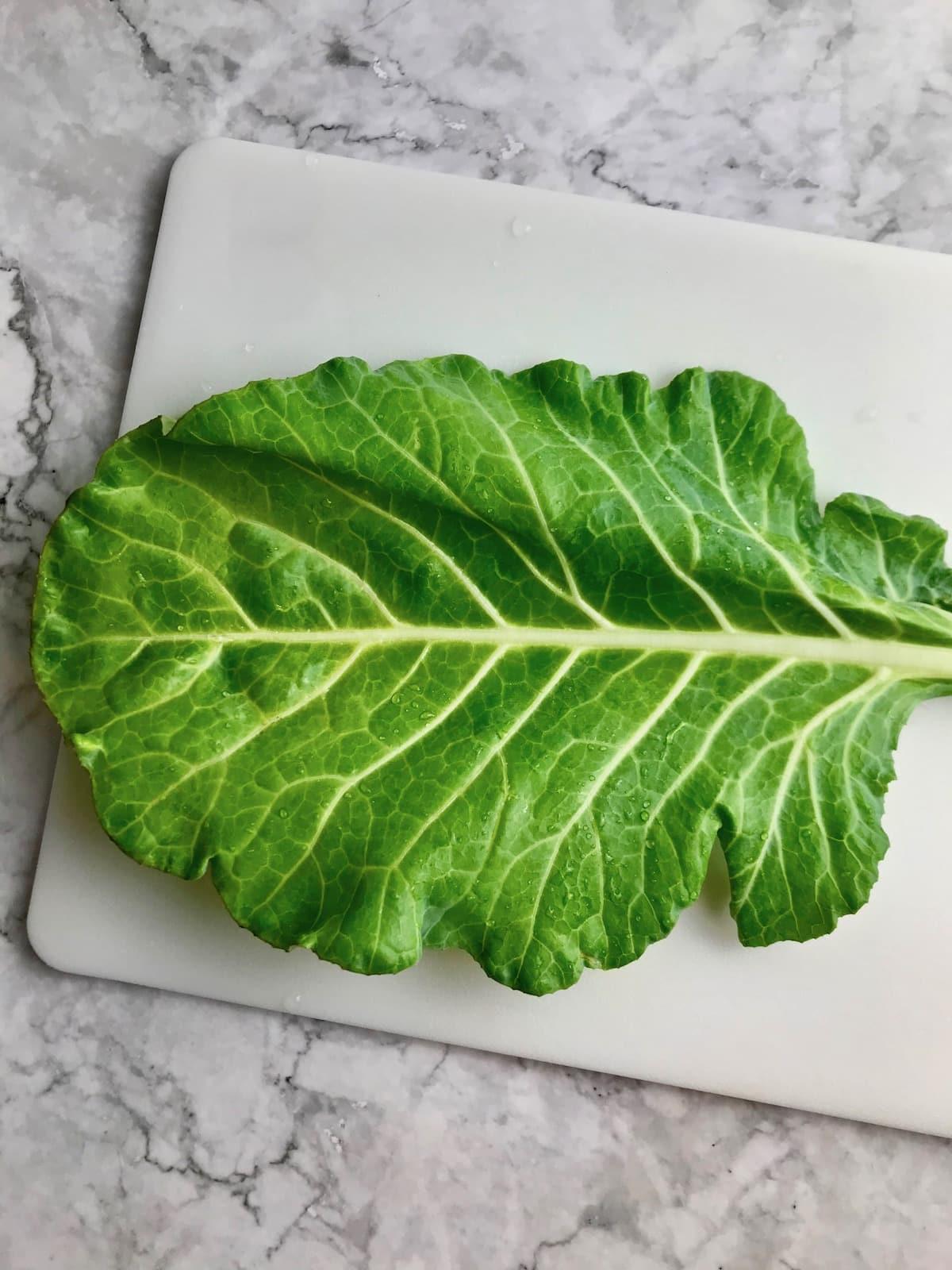 A collard leaf on a cutting board.