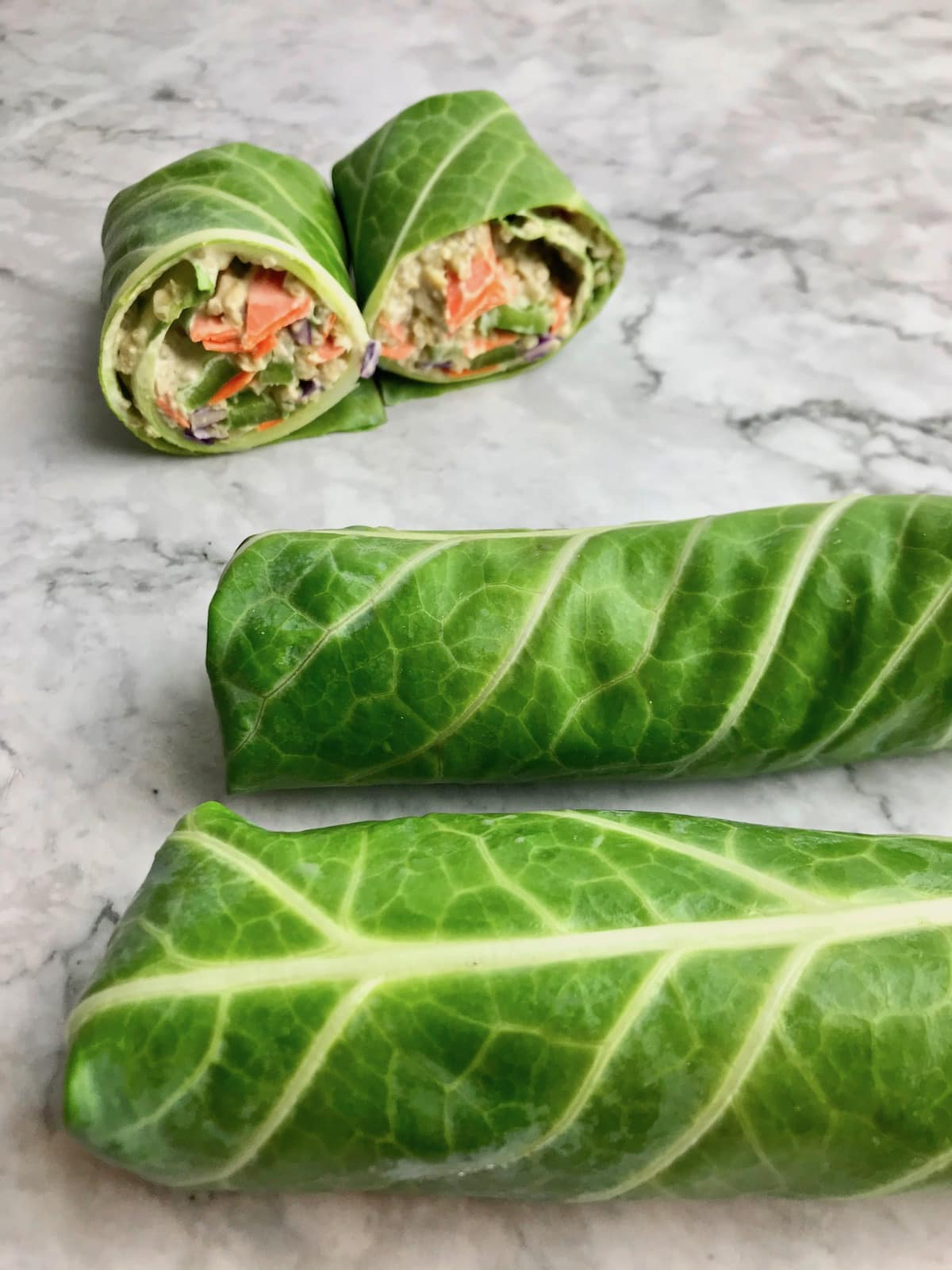 Two rolled up collard wraps and one cut in half collard wrap with a quinoa vegetable filling.
