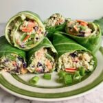 Collard green wraps on a plate, filled with quinoa and vegetables.