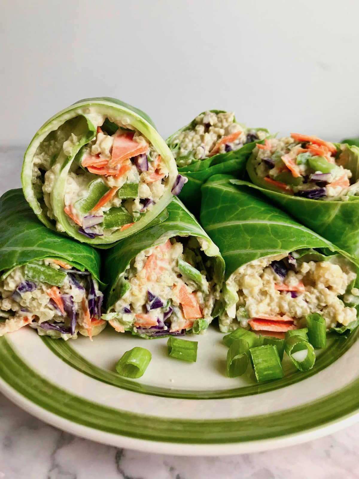A pile of vegan collard green wraps on a plate, filled with quinoa and veggies.