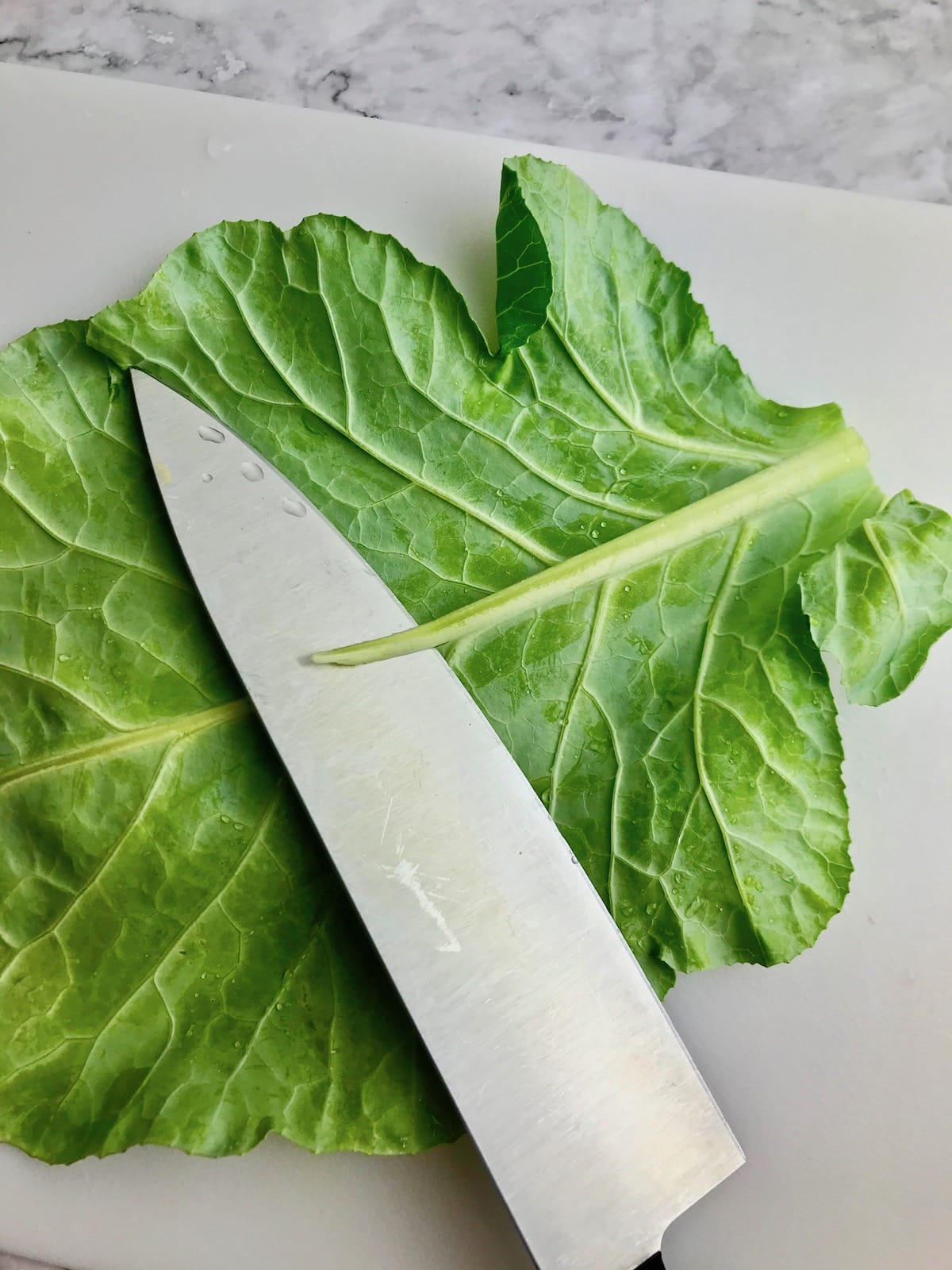 A knife slicing off the stem along the center of a collard leaf.