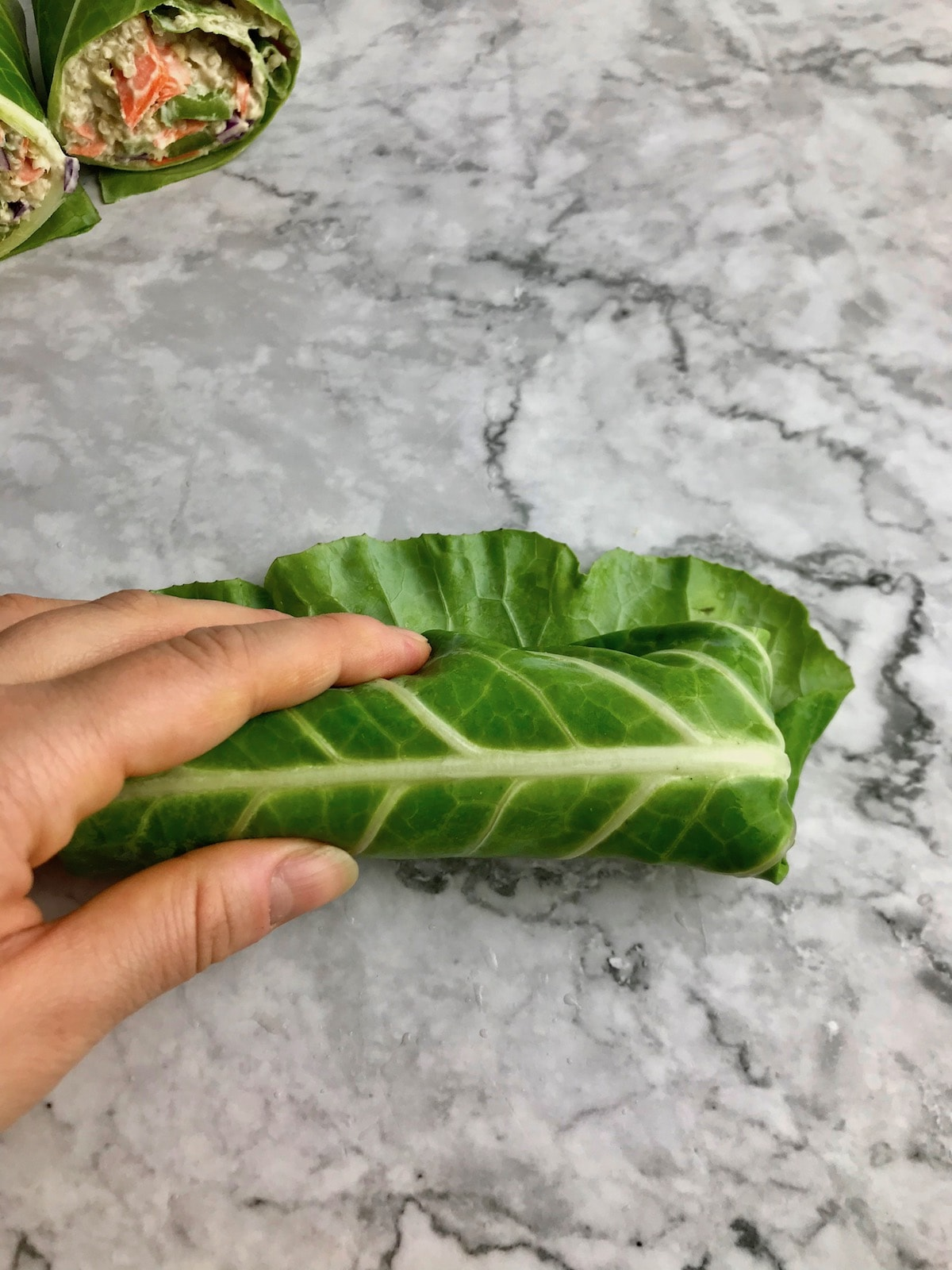 A hand holding a rolled up collard wrap on a table.