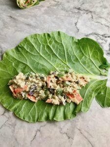A collard leaf with quinoa and vegetables laid on top of it.