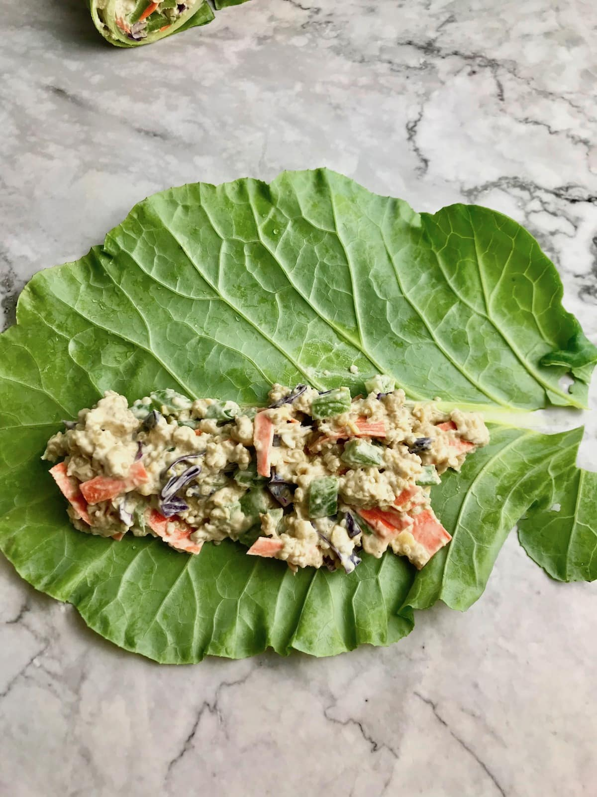 A collard green leaf with chickpea quinoa filling on it lengthwise.