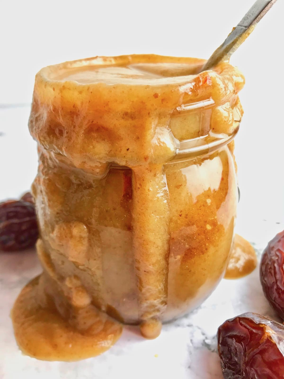 Vegan caramel sauce overflowing in a glass jar, surrounded by dates on a table.