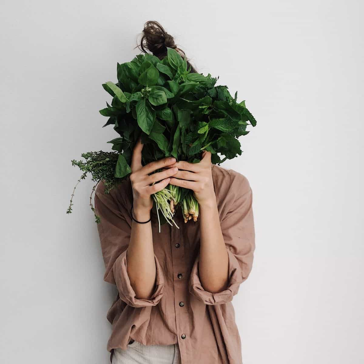 A woman holding leafy green vegetables in front of her face.