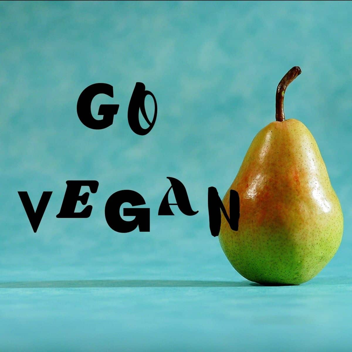 """A pear next to text that says, """"Go Vegan."""""""