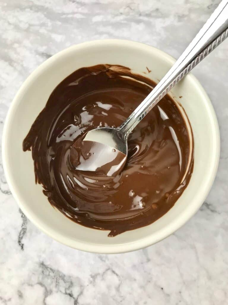 Melted chocolate in a small bowl with a spoon.