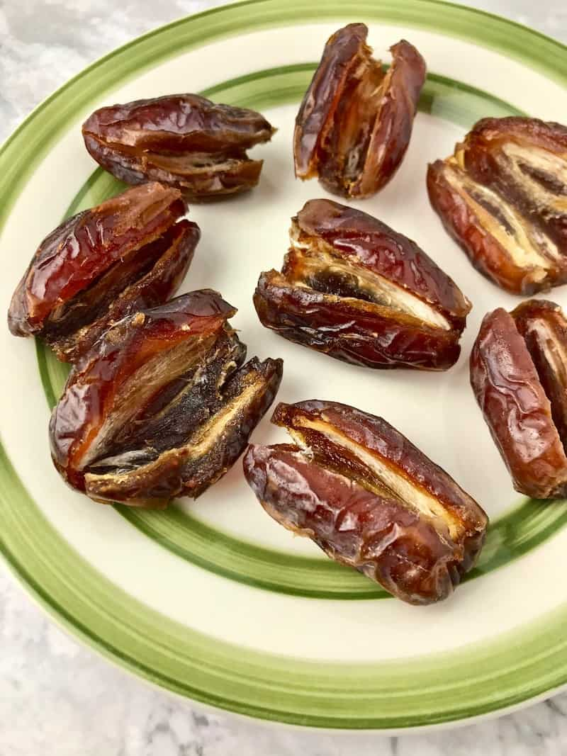 A plate of Medjool dates that are open lengthwise.
