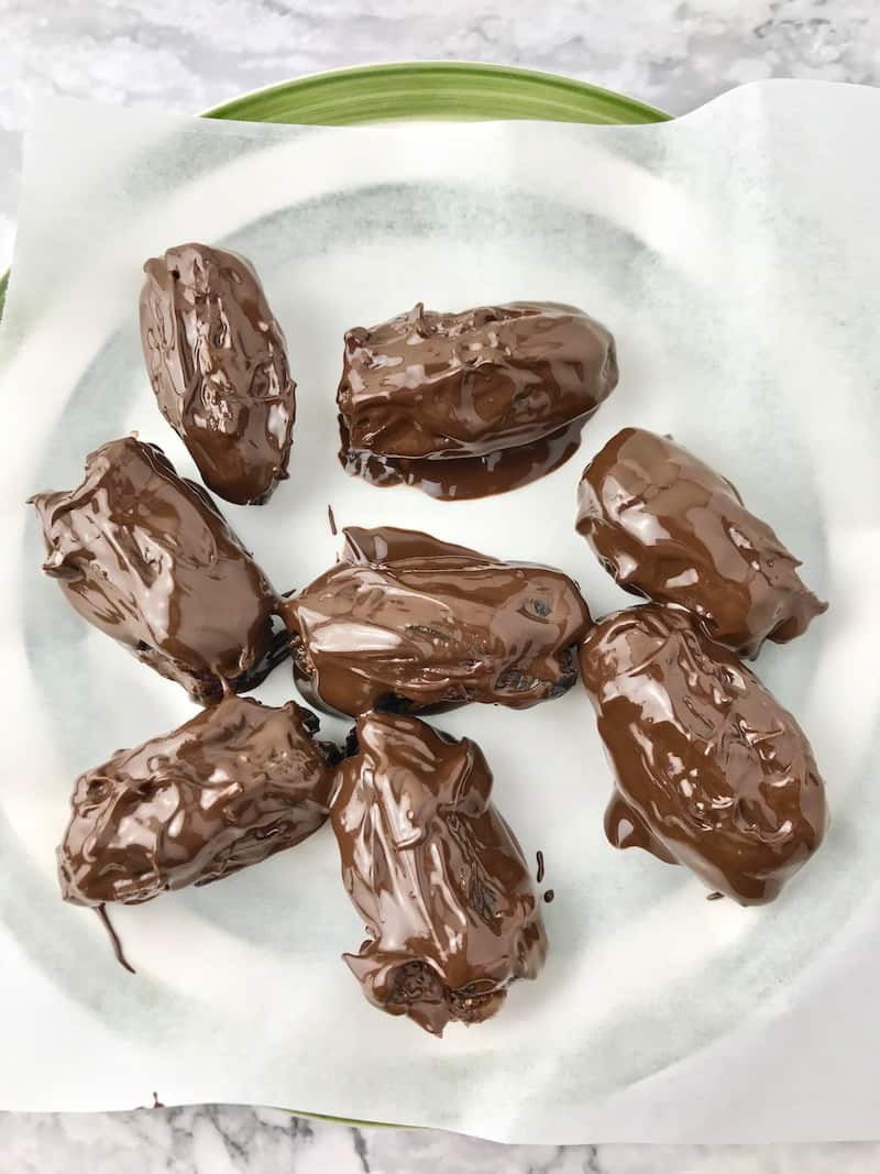 Dates dipped in melted chocolate, sitting on a parchment lined plate.
