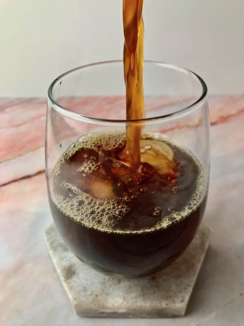 Coffee being poured into a glass with ice.