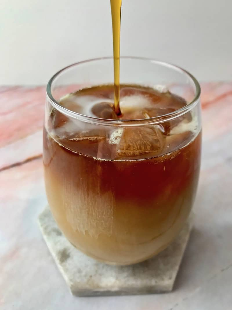 Maple syrup being poured into a glass of iced coffee.