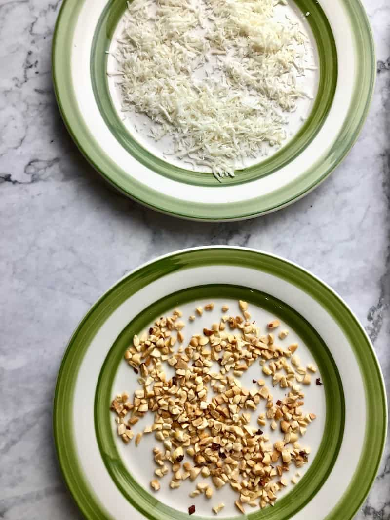 A plate of chopped peanuts next to a plate of coconut flakes.