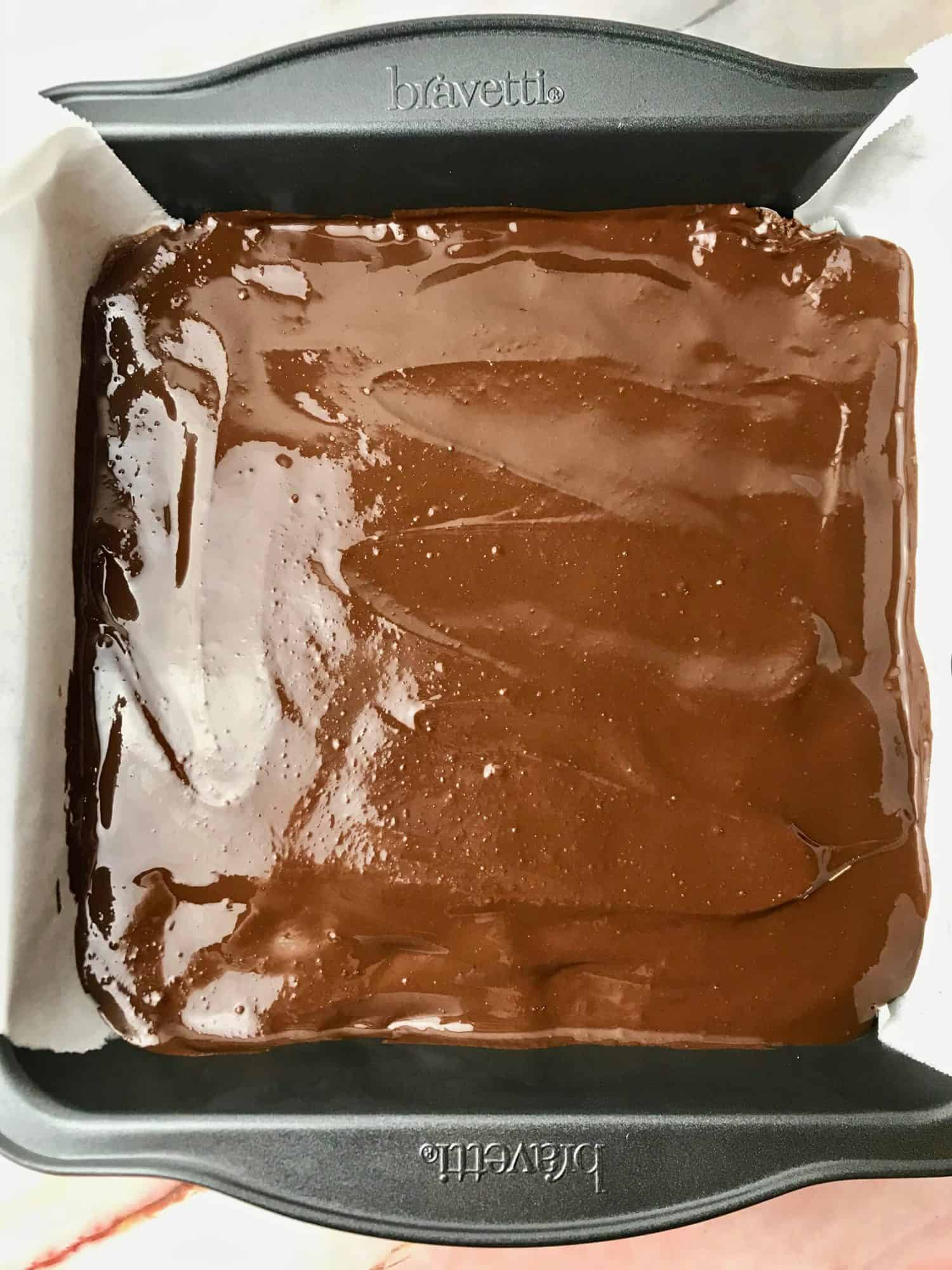 Melted chocolate spread over dough in a square pan.