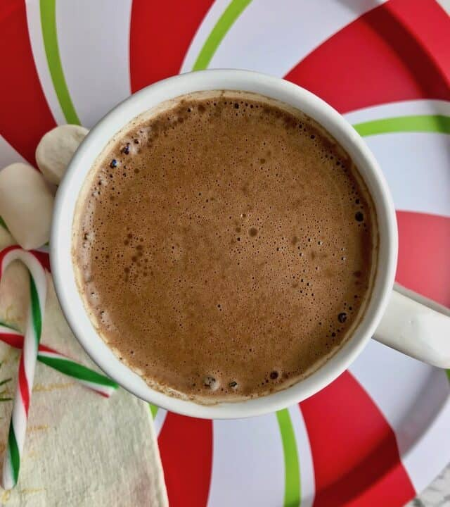 Hot chocolate on a red, white, and green striped tray.