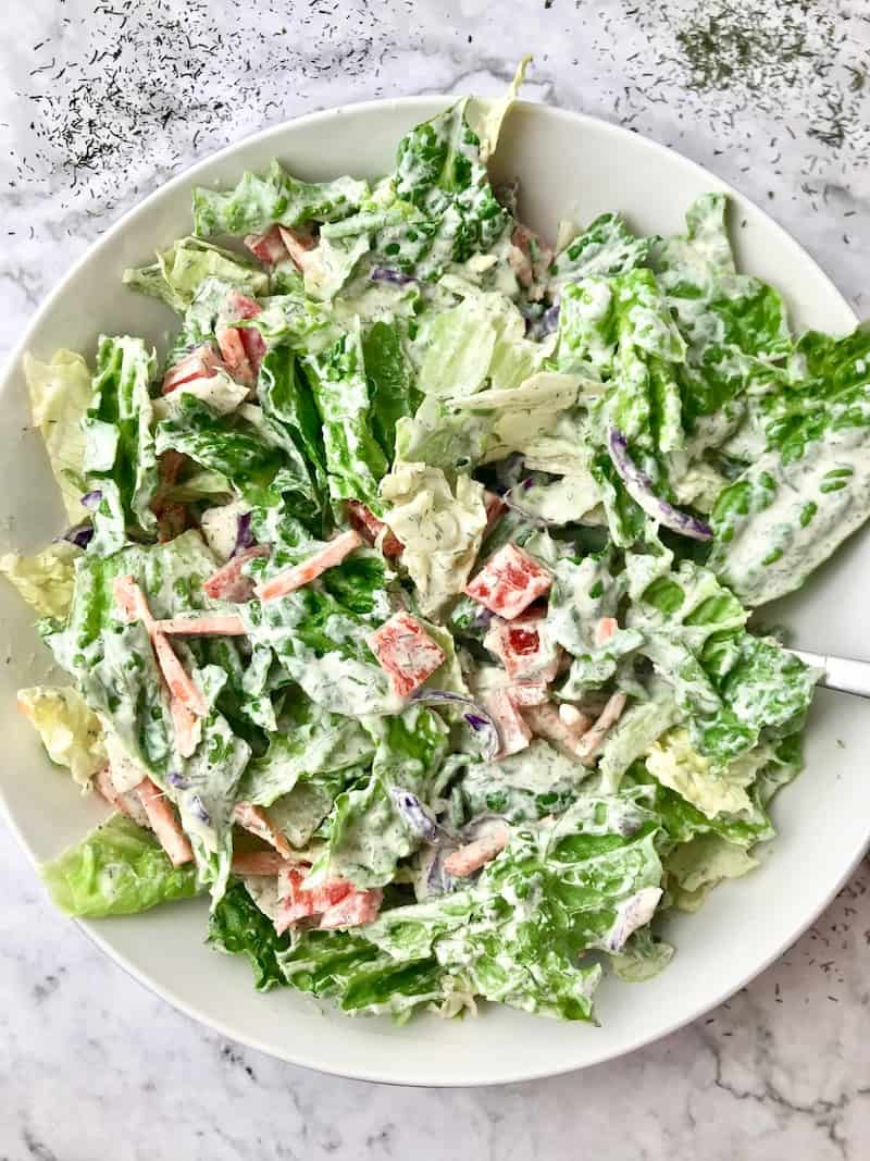 A salad covered in a white dill dressing.