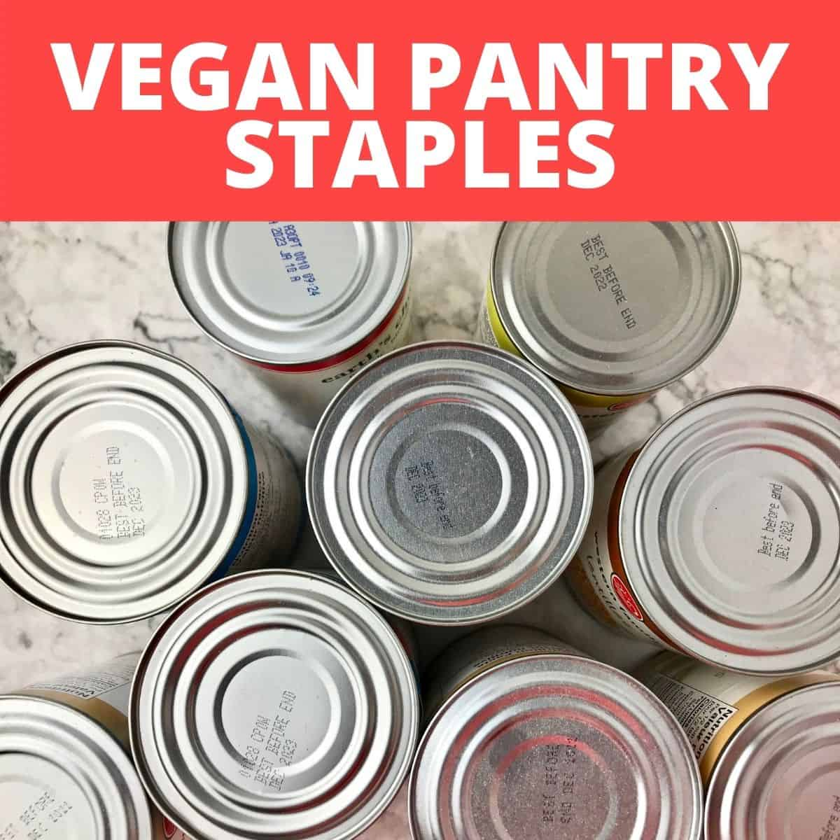 """The tops of several tin cans below text that says, """"Vegan Pantry Staples."""""""