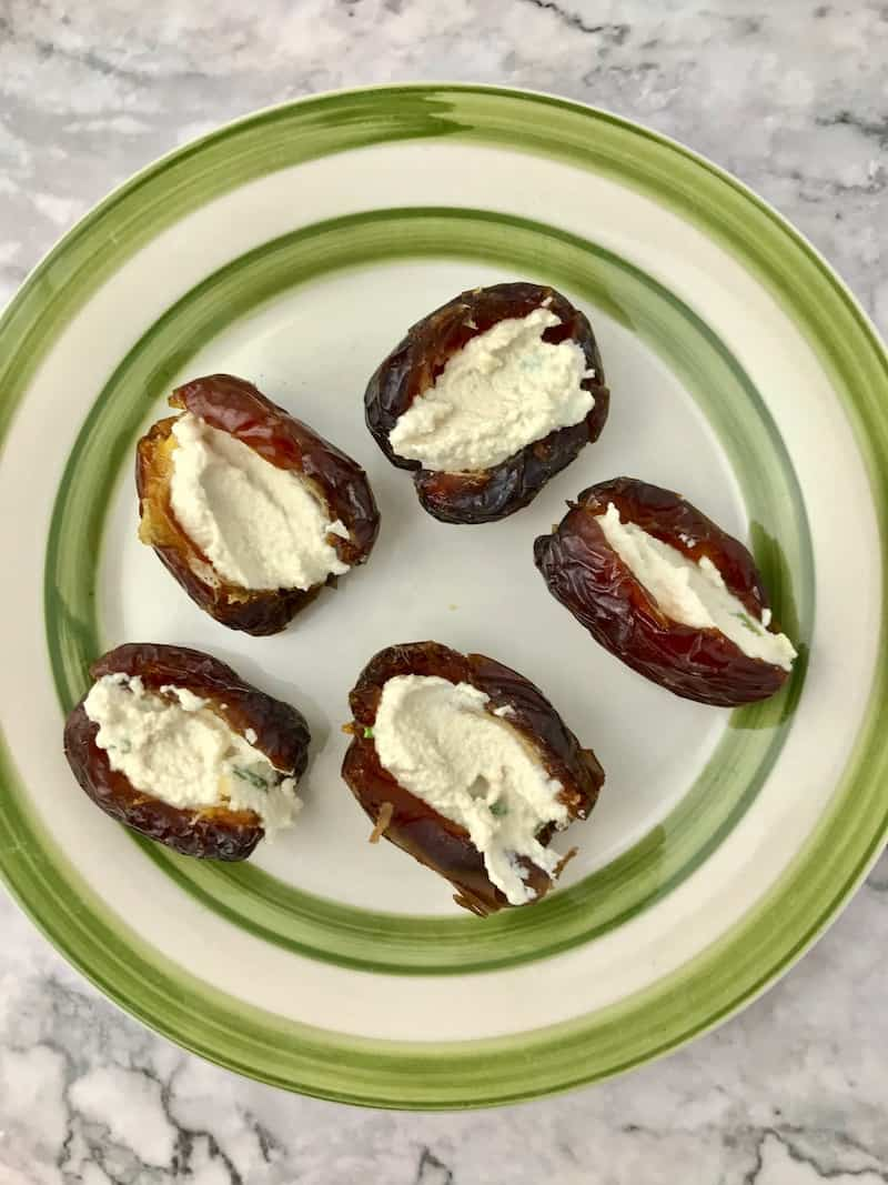 Medjool dates stuffed with vegan cream cheese, on a green and white plate.