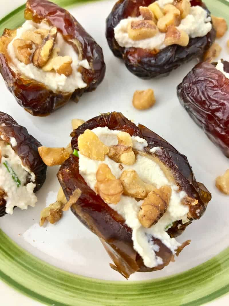 Dates with cream cheese and walnut pieces on a green and white plate.