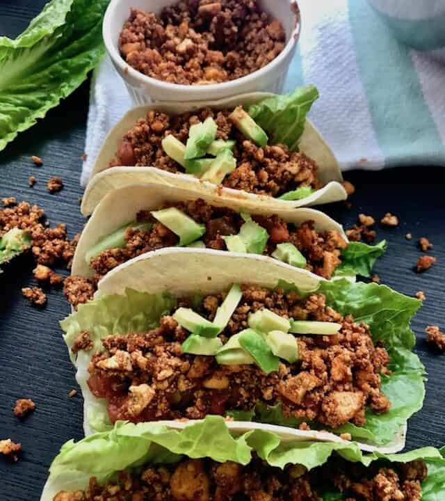 Four tofu tacos in front of a small bowl of tofu crumbles.