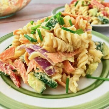 A plate of hummus pasta salad topped with chopped chives.