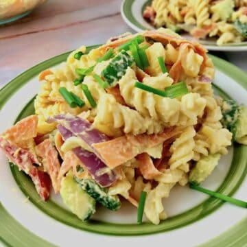 A plate of pasta salad topped with creamy hummus.