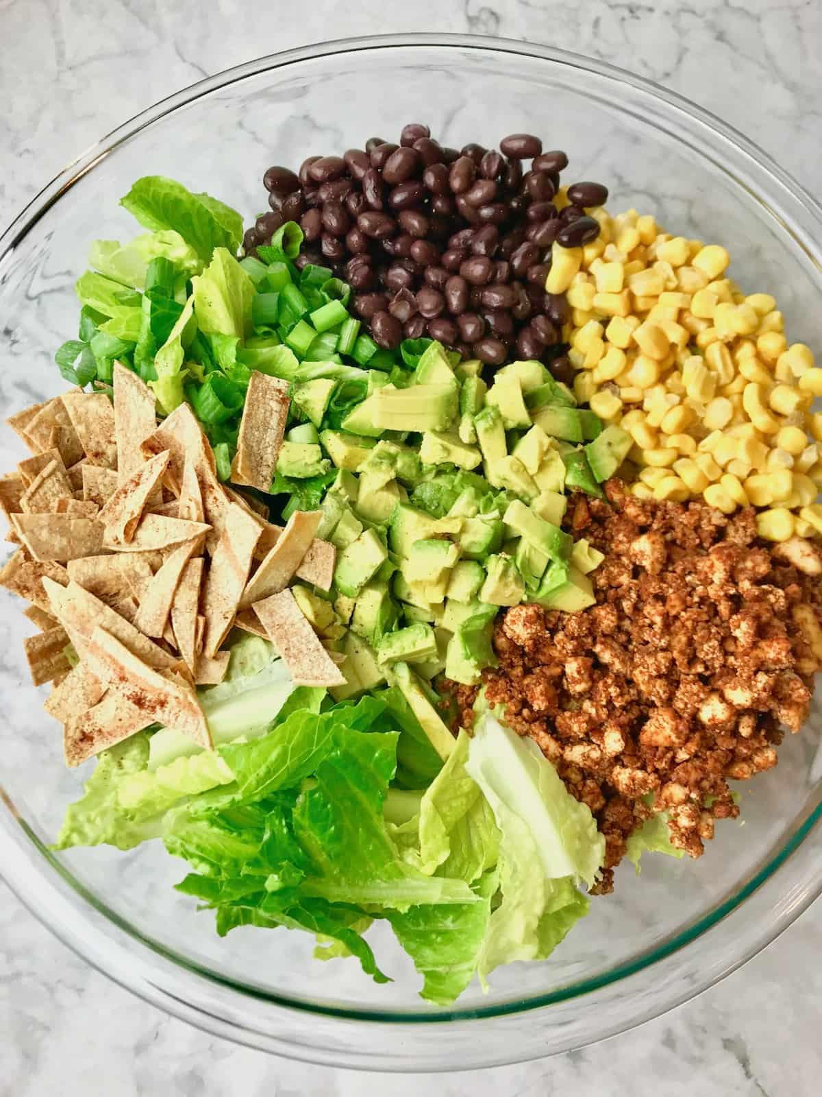 Black beans, corn, tofu, lettuce, tortilla strips, avocado, and lettuce in a bowl.
