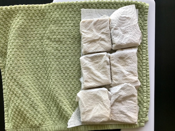 Slices of tofu wrapped in paper towel, sitting on a dish towel.