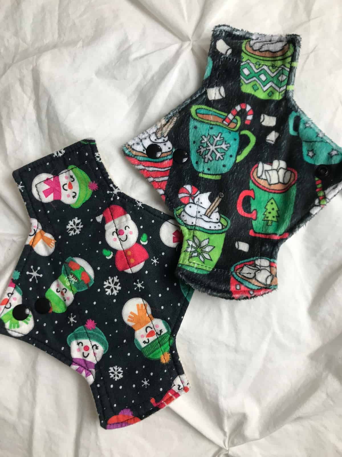 Two reusable menstrual pads with Christmas patterns on them.