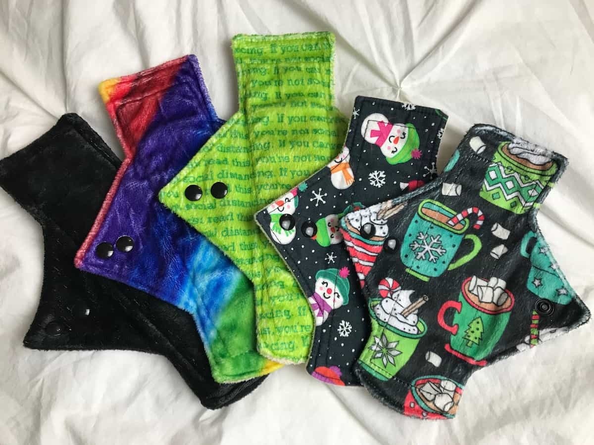 Five different reusable cloth pads on a white background.