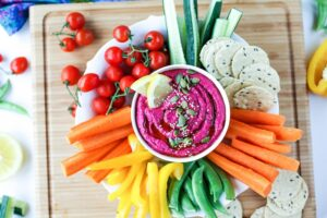 Beet hummus surrounded by chopped raw vegetables and crackers.