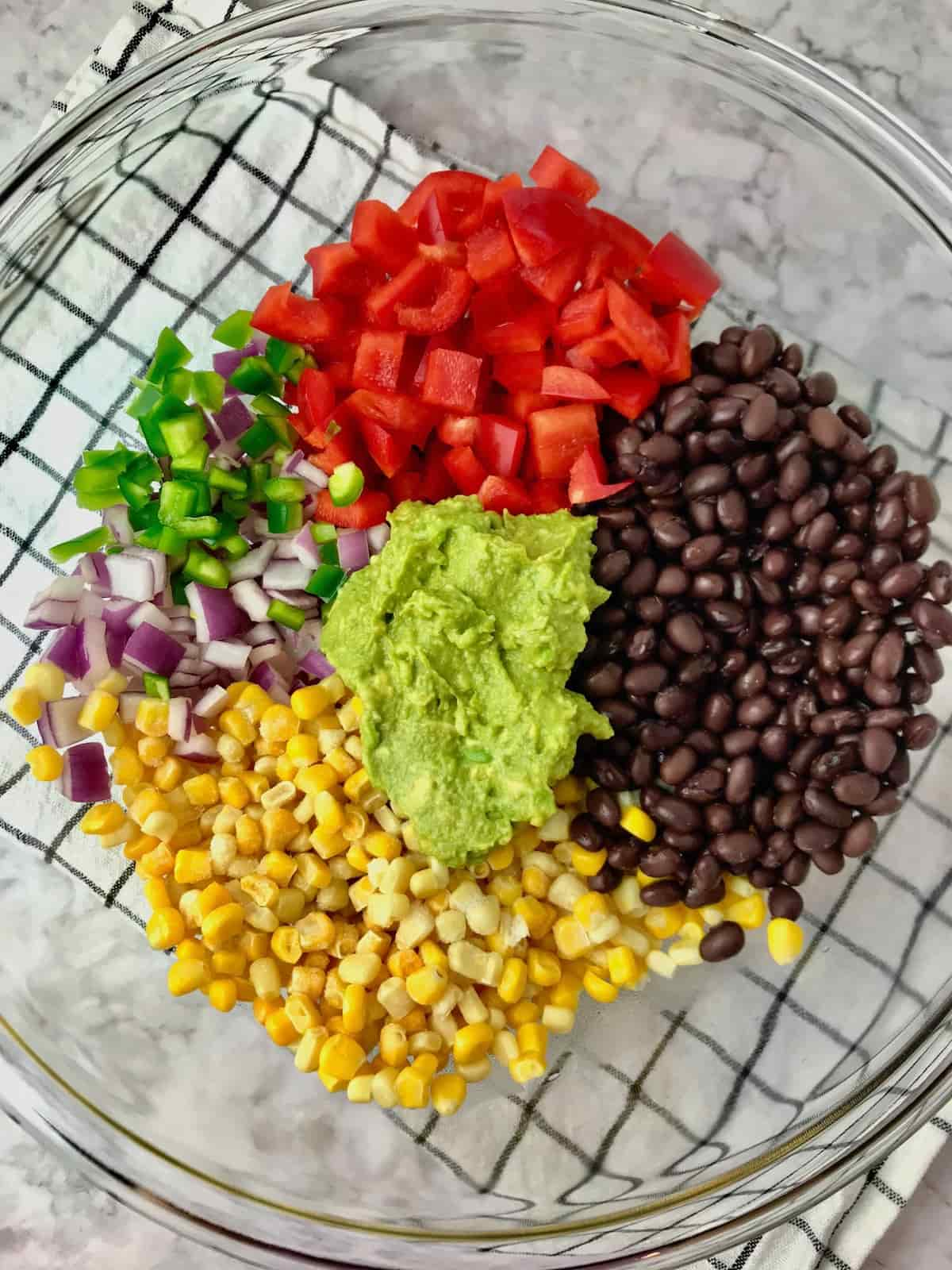 A bowl with red pepper, red onion, corn, black beans, jalapeno pepper and avocado.