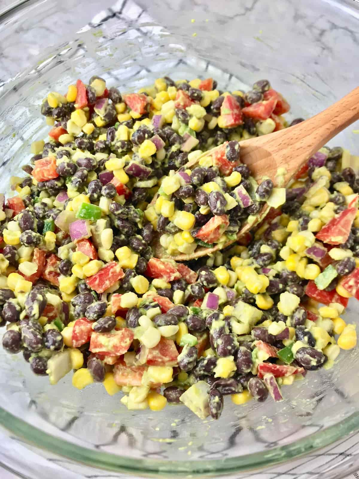 A large clear bowl full of black bean and corn salad with a wooden spoon.