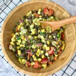 A bowl of black bean and corn salad with a wooden spoon in it.