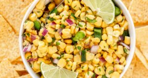Corn salsa in a bowl with lime wedges, surrounded by chips.