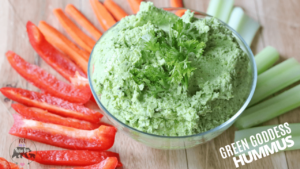 A green kale dip next to some raw veggies.