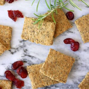 Crackers on a surface next to some cranberries.