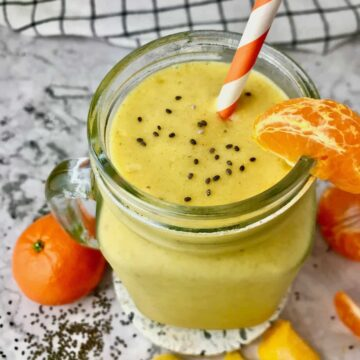 A smoothie in a mason jar with an orange slice on the rim and chia seeds sprinkled on top.