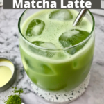 An oat milk iced matcha latte in a stemless wine glass with a metal straw in it.