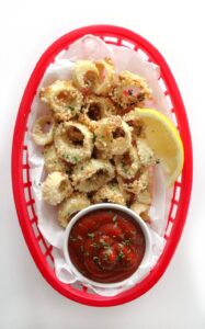 Vegan calamari in a container next to a lemon wedge and a bowl of ketchup.