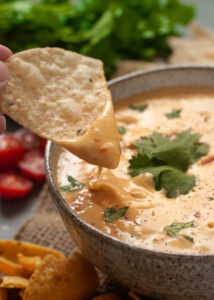 Vegan queso dip with a tortilla chip dipped into it.