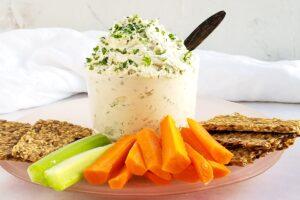 Garlic vegan cream cheese next to raw veggies and crackers.